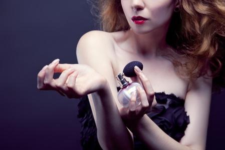 beautiful woman applying perfume on her body