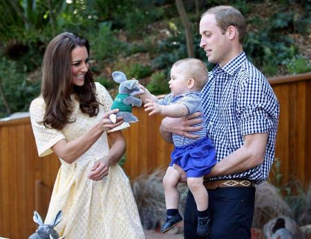 Prince William holds Prince George as Catherine, Duchess of Cambridge, gives him a toy during a visit to the Bilby Enclosure at Sydney's Taronga Zoo
