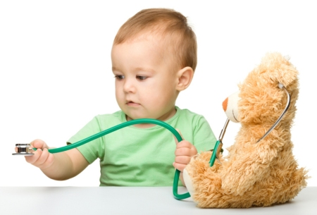 Cute little boy is playing doctor with stethoscope and teddy bear, isolated over white