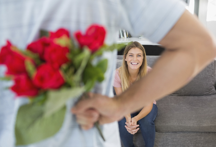 Man hiding bouquet of roses from girlfriend on the couch in sitting room at home